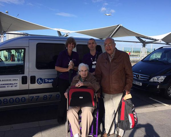 An elderly couple pose in front of a Transmobility van at an airport