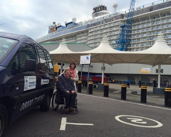 A man in a wheelchair and a female pose in front of a cruise ship