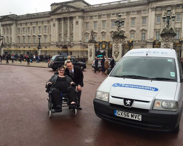 A woman in a wheelchair poses for a picture outside of Buckingham Palace alongside a Transmobility van